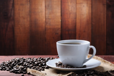 white cup with coffee beans on the wooden table photo