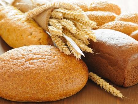 bolsa de pan: rodajas de pan y trigo en la mesa de madera