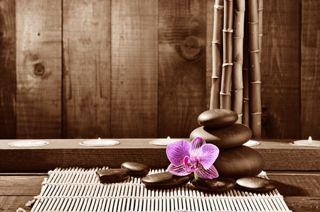 zen candles: spa frame from bamboo grove, pink orchid and black zen stones on the old wooden background Stock Photo