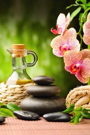 Zen Basaltsteinen und Orchideen auf dem Holz Standard-Bild