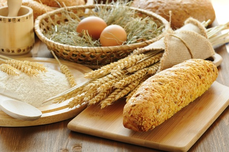 utensilios de cocina: rebanadas de pan y trigo en la mesa de madera