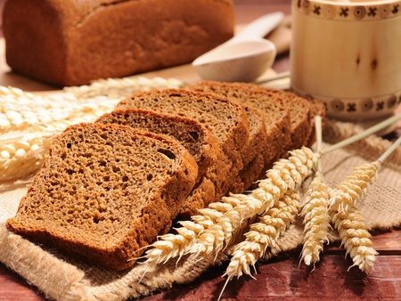 bread and wheat on the wooden background photo