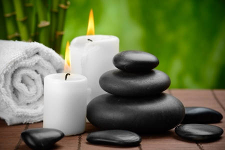 bamboo therapy: zen basalt stones and candle on the wooden mat
