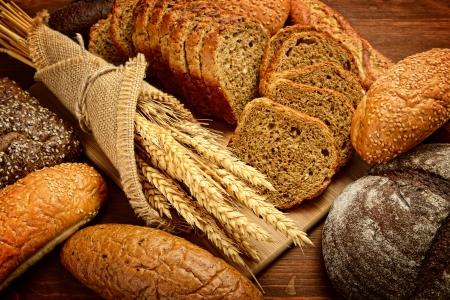 cultivo de trigo: pan fresco y trigo en la madera Foto de archivo
