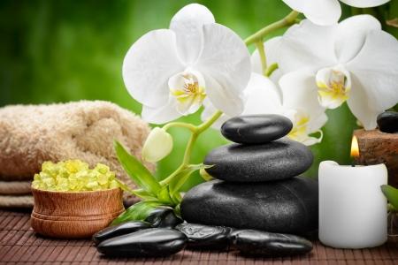 massaggio: pietre di basalto Zen e orchidea sul legno