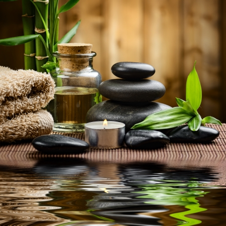 spa therapy: zen basalt stones and spa oil on the wood Stock Photo