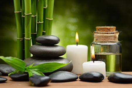 masaje: zen piedras de basalto y el aceite de spa en la madera