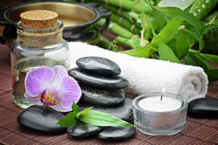 bamboo therapy: zen basalt stones and orchid on the wood Stock Photo