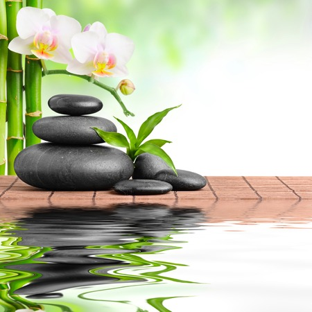 bamboo mat: zen basalt stones and orchid Stock Photo