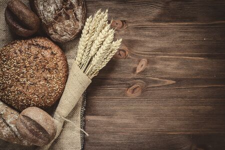 bakery products: fresh bread  and wheat on the wooden