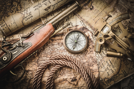 books on a wooden surface: vintage  still life with compass,sextant and pistol Stock Photo