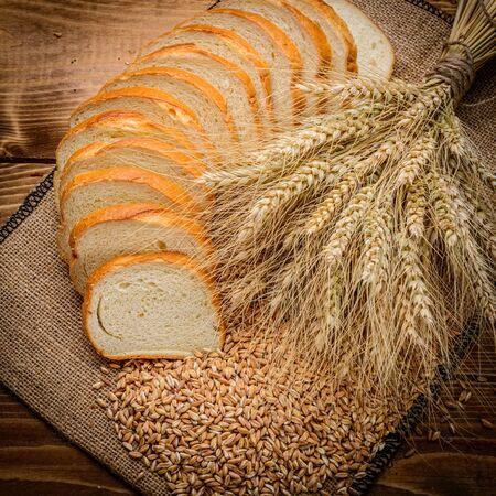 bollos: pan fresco y trigo en la madera Foto de archivo