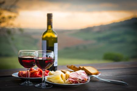 vino: naturaleza muerta Rojo vino, queso y jamón. Cena romántica al aire libre