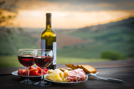 romantic: still life Red wine  ,cheese and prosciutto. Romantic dinner  outdoors