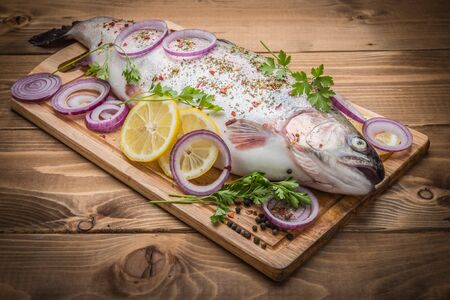 raw: Rainbow trout with fresh spices on the wooden