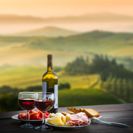 picnic table: still life Red wine  ,cheese and prosciutto. Romantic dinner  outdoors
