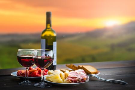 italienisches essen: Stilleben Roter Wein, Käse und Schinken. Romantisches Abendessen im Freien Lizenzfreie Bilder