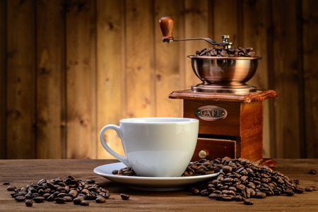 grano de cafe: Todavía vida con los granos de café y molino de café antiguo en el fondo de madera Foto de archivo