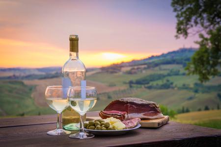 静物白ワインとチーズと生ハム。屋外のロマンチックなディナー