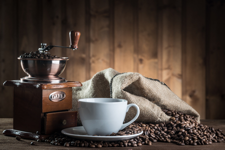 composition: still life with coffee beans and old coffee mill on the wooden background