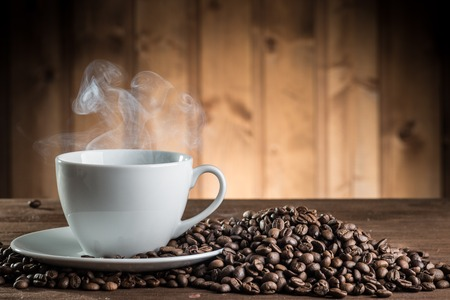 still life with coffee beans and cup on the wooden background