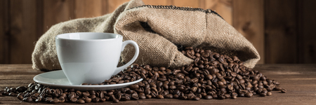 složení: Zátiší s kávovými zrny a šálkem na dřevěném pozadí