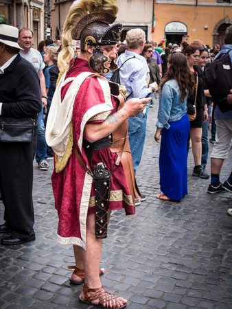 Rome, Italy, circa June 2013   Roman soldier sending a text message in the street, in full regalia