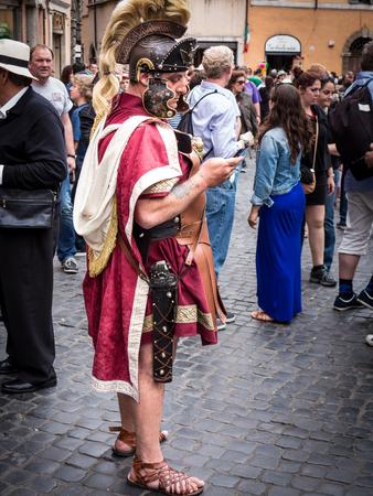 regalia: Rome, Italy, circa June 2013   Roman soldier sending a text message in the street, in full regalia