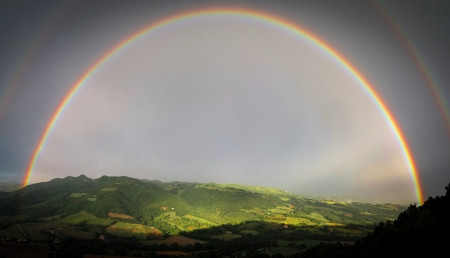 Full double rainbow with sunlit hills and fields through the arc of the rainbow Imagens