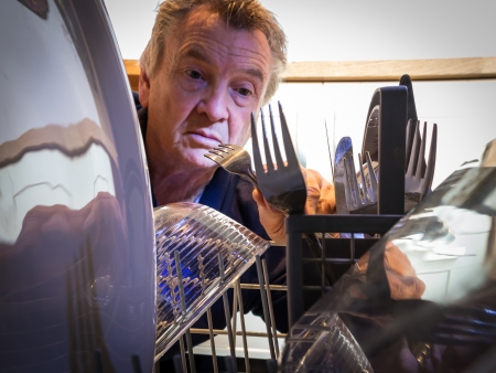 Senior man loading or unloading the dishwasher with clean crockery and cutlery from the inside of the machine looking out photo