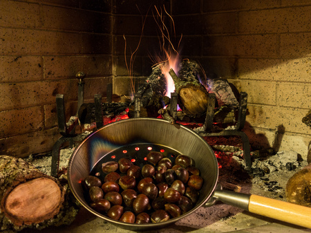 Chestnuts in a pan roasting on a glowing fire with flames and embers