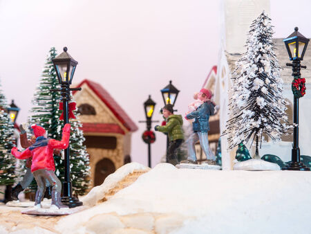 dollhouse: A large and detailed closeup of a Christmas Village  Children playing snowballs in the illuminated street outside the Church  Shallow depth of field