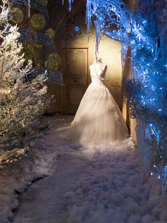 Winter window dressing of a retail shop with blue lights and snow with an elegant dress on a mannequin photo