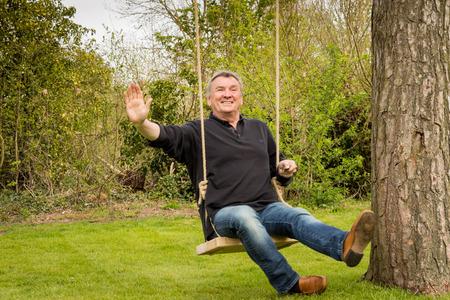 Senior man on a tree swing in the garden Imagens