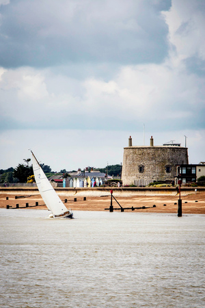 Yacht navigating the river at speed by the martello tower