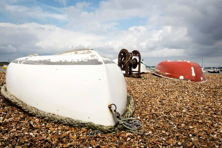 Upturned row boats and mooring winch Imagens