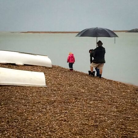 Family at the beach on a rainy English summer day Imagens