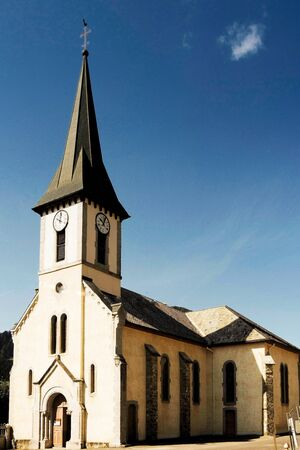 The church at La Côte-dArbroz in France with spire reaching into a blue summer sky Imagens