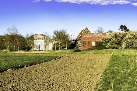 Abandoned old barns and sheds next to a ploughed field