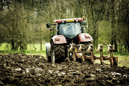plough machine: Tractor turning the earth in a field in springtime