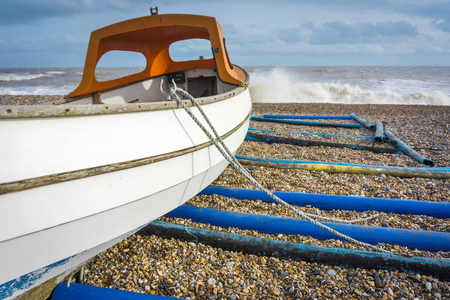 Small boat moored on a windy beach Imagens