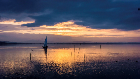 Yacht sailing at sunset with cloudscape Imagens