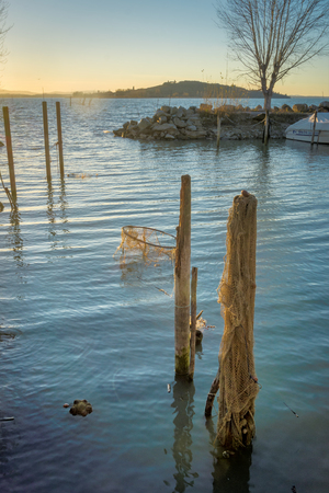 Jetty posts and fishing nets in the lake Imagens