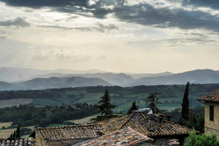 Italian mountains and valleys across the roof tops of a village Imagens