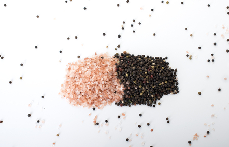 Himalayan rock salt and peppercorns, set against a white background