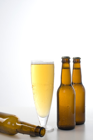 Glass of beer with 2 beer bottles set against a white background