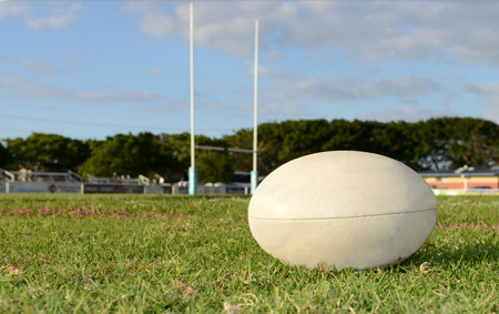 Rugby Ball on grass in front of goal post.