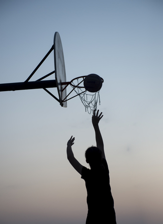 Basketball Player Silhouette shooting a basketball at the hoop