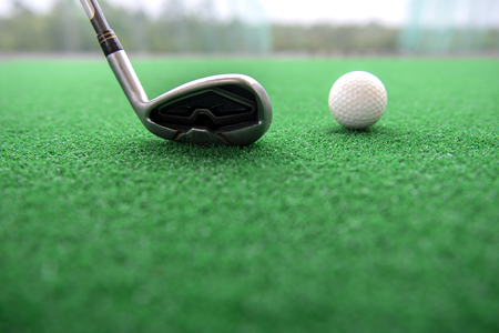 Golf club and ball on a synthetic grass mat at a practice range.