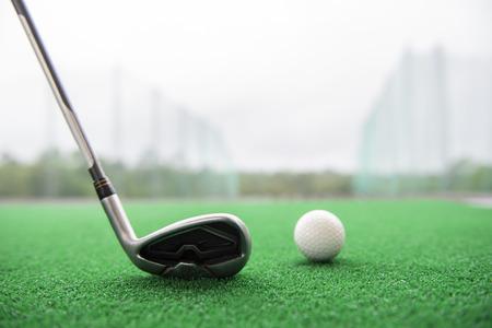 Golfclub und Ball auf einer Kunstrasenmatte an einem Übungsplatz.